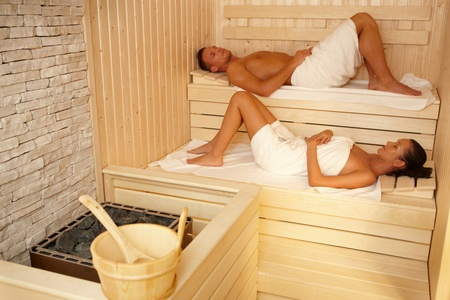 Couple lying in sauna wearing towel, relaxing with eyes closed. photo