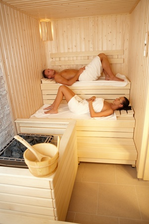 lay down: Man and woman lying in sauna, relaxing on wellness.