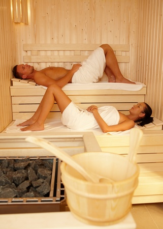 Relaxing in sauna, young couple enjoying healthy wellness. photo