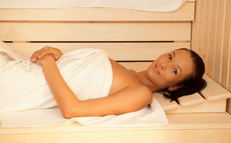 Portrait of happy woman lying in sauna, relaxing. photo