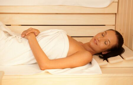 Woman enjoying sauna, lying with eyes closed, relaxing in healthy wellness. photo
