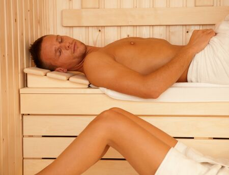lay down: Sauna relaxation, sporty man lying, enjoying healthy heat.