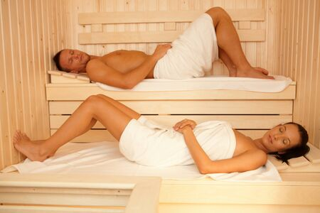 lay down: Portrait of couple in sauna, lying on towels with eyes closed, relaxing.