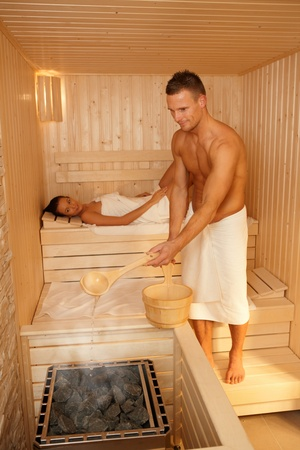 lay down: Couple using sauna, man making steam, smiling, woman lying in background. Stock Photo