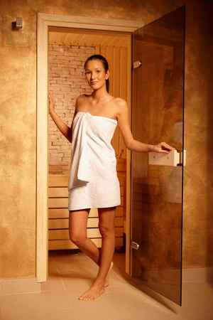 Pretty woman wearing towel standing at door of sauna, smiling at camera, photo