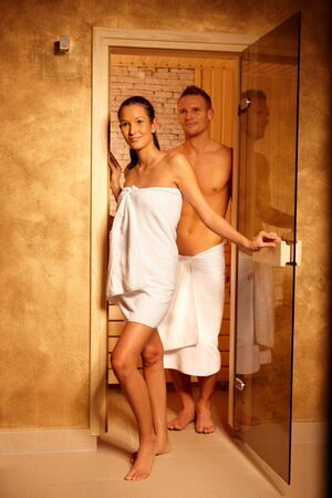 Couple standing at sauna door, smiling after relaxing in steam, leaving.