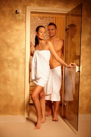 Happy couple standing at sauna door on healthy wellness program. photo