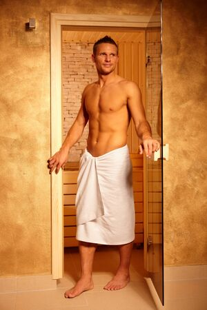 Portrait of sporty handsome man leaving sauna, semi-nude in towel, smiling, Stock Photo - 8753427