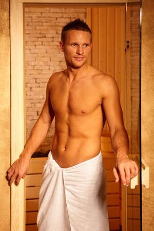 Athletic man standing at sauna door, leaving healthy steam. Stock Photo - 8753397