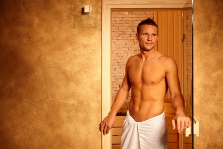 Happy man leaving steam after healthy sauna, athletic guy in wellness. photo