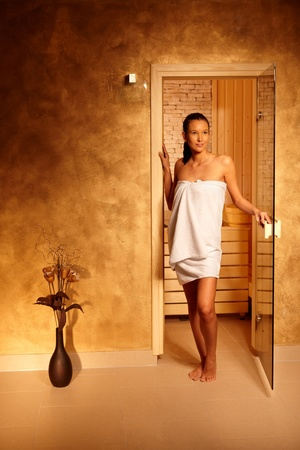 adult only: Young happy woman leaving sauna, standing at door in towel, smiling. Stock Photo