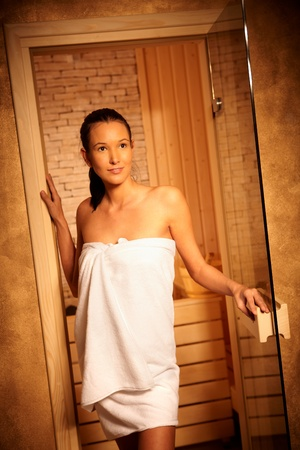 Attractive woman wearing towel posing at entrance of sauna, opening door, smiling. photo