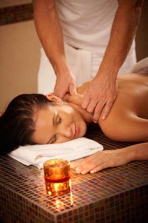 homme massage: Jeune femme jouissant de massage avec les yeux ferm�s en environnement de bien-�tre.