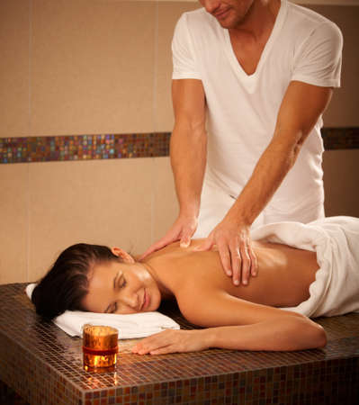Young woman getting back massage in wellness center, relaxing with eyes closed. photo