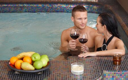 a pair of: Young couple enjoying relaxation in spa with glass of wine. Stock Photo