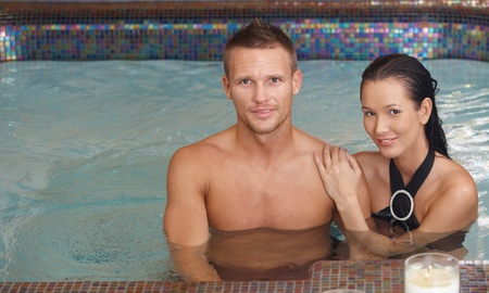 Portrait of loving couple in swimming pool, smiling at camera. photo