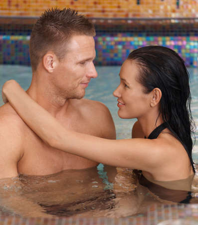 Happy couple in love embracing in wellness spa, smiling. photo