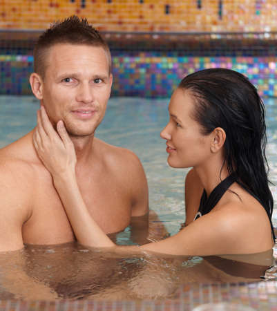 Happy couple on wellness program, relaxing in spa, woman caressing smiling man. photo