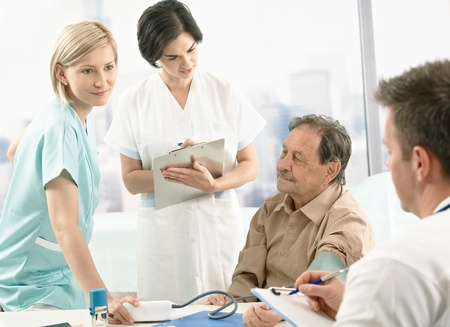 Medical team measuring blood pressure of senior patient, nurse assisting, doctors taking notes on clipboard. Stock Photo - 8783006