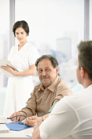 Older patient at consultation with doctor, nurse standing in background. Stock Photo - 8782820