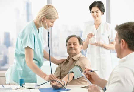 Verpleegkundige onderzoek bloeddruk voor patiënt, artsen wachten op resultaten.