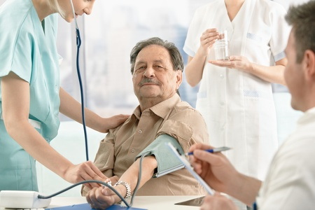 Patient getting blood pressure measurement, nurse and doctor examining. Stock Photo - 8783192