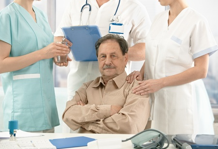 Old patient sitting on doctors room, nurse and doctors standing around. photo