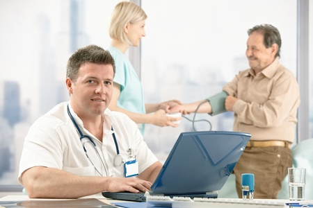 Portrait of mid-adult medical doctor sitting at desk, nurse measuring blood pressure of older patient in background. Stock Photo - 8782901