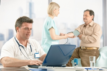 color consultant: Mid-adult doctor sitting at desk looking at computer, nurse measuring blood pressure of older patient in office.