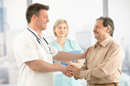 Smiling medical doctor shaking hands with happy senior patient, nurse in background.
