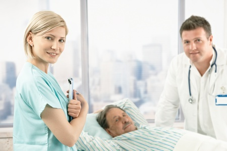 Portrait of hospital nurse at work, smiling at camera, doctor and patient in background. Stock Photo - 8782773