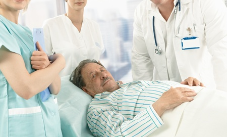 sick day: Elderly male patient lying in hospital bed wearing pyjama, medical team around. Stock Photo