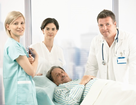 Portrait of senior patient lying in bed, surrounded with hospital crew, smiling at camera. Stock Photo - 8782708
