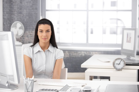 Portrait of pretty girl sitting at desk in bright office, smiling at camera. Stock Photo - 8782709