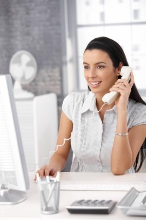 secretary woman: Happy office girl at desk working on desktop computer, using landline phone, smiling.