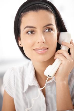 Closeup portrait of beautiful woman with landline phone handheld, smiling. Stock Photo - 8782944