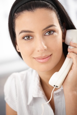 handheld: Portrait of smiling attractive woman with landline phone handheld, looking at camera. Stock Photo