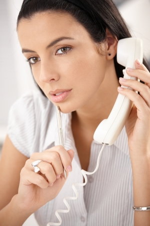 Attractive woman concentrating on landline phone call, thinking, holding pen. Stock Photo - 8783190