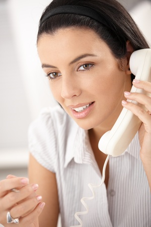 Beauty with dark hair on landline call, gesturing, smiling. Stock Photo - 8783087