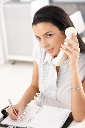 taking note: Pretty girl office lavorano alla scrivania, tenendo note personali organizzatore, concentrandosi sulla chiamata di telefono di rete fissa. Archivio Fotografico