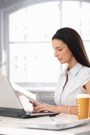 Businesswoman reviewing document at desk, using laptop computer, smiling, takeaway coffee. photo