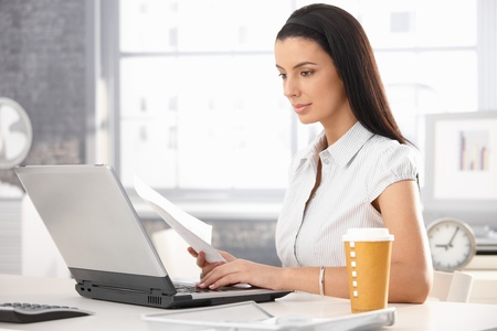Attractive woman sitting at desk in office, working with laptop computer, holding document, having takeaway coffee. Stock Photo - 8782721