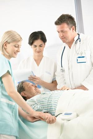 Doctors and nurse examining old patient in hospital, nurse measuring blood pressure. photo