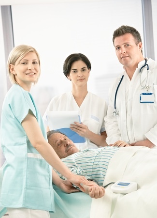 Portrait of medical team with old patient in hospital, smiling nurse measuring blood pressure. Stock Photo - 8782706