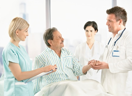 man doctor: Medical crew talking to old patient in hospital, doctor holding his hand. Stock Photo