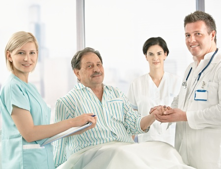 Medical team taking care of elderly patient sitting on hospital bed in pyjama, holding hands. Stock Photo - 8782777