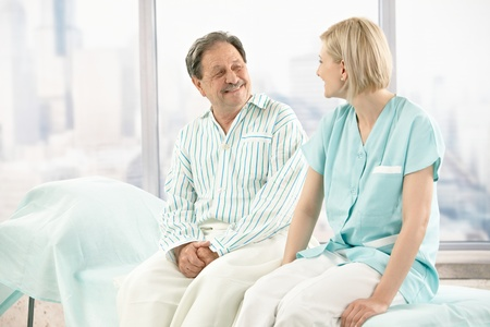 Older patient wearing pyjama in hospital, talking to nurse, smiling. photo