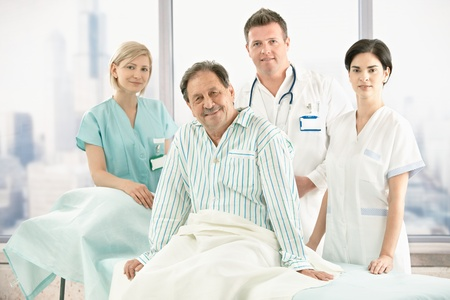 Older patient sitting on bed with hospital crew in background. photo