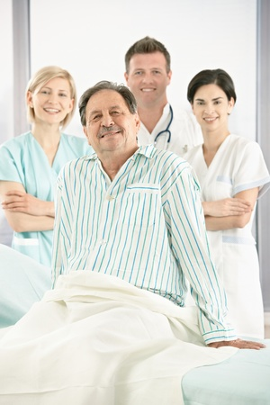 eye care professional: Portrait of smiling medical team with senior patient in hospital. Stock Photo