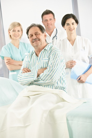 Elderly patient in hospital smiling at camera with medical team in background. Stock Photo - 8782833